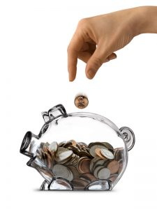 A females hand dropping a coin into a clear piggy bank half filled with coins.